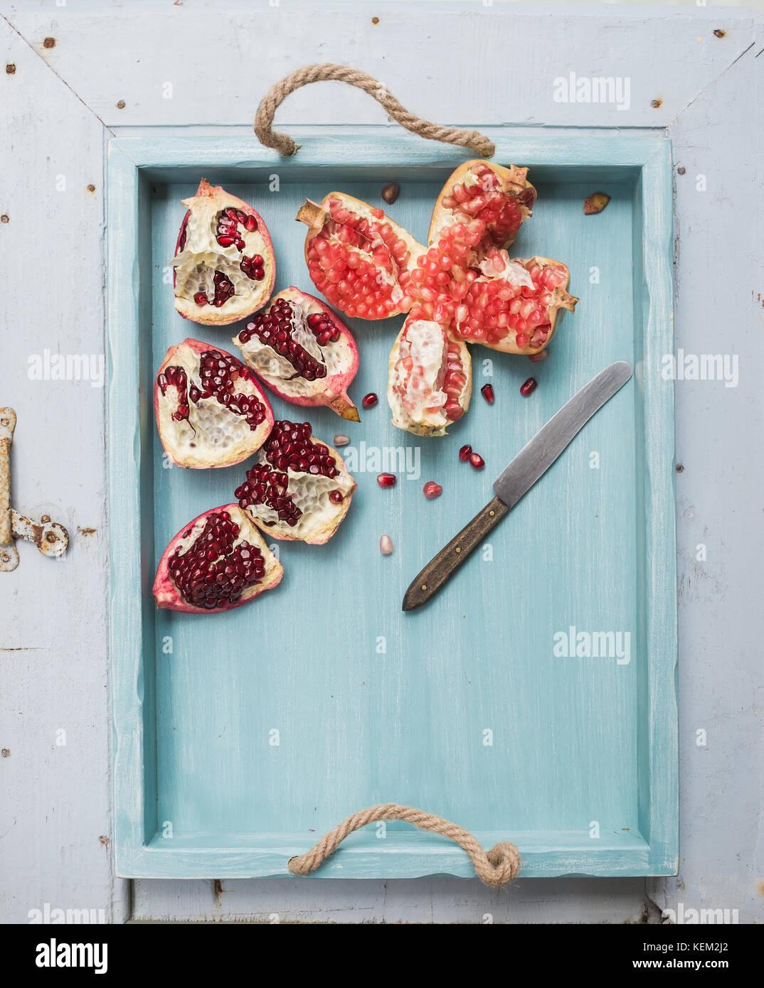 Le rouge et le blanc des grenades et le couteau dans le bac bleu en bois peint sur toile de lumière, vue du Photo Stock