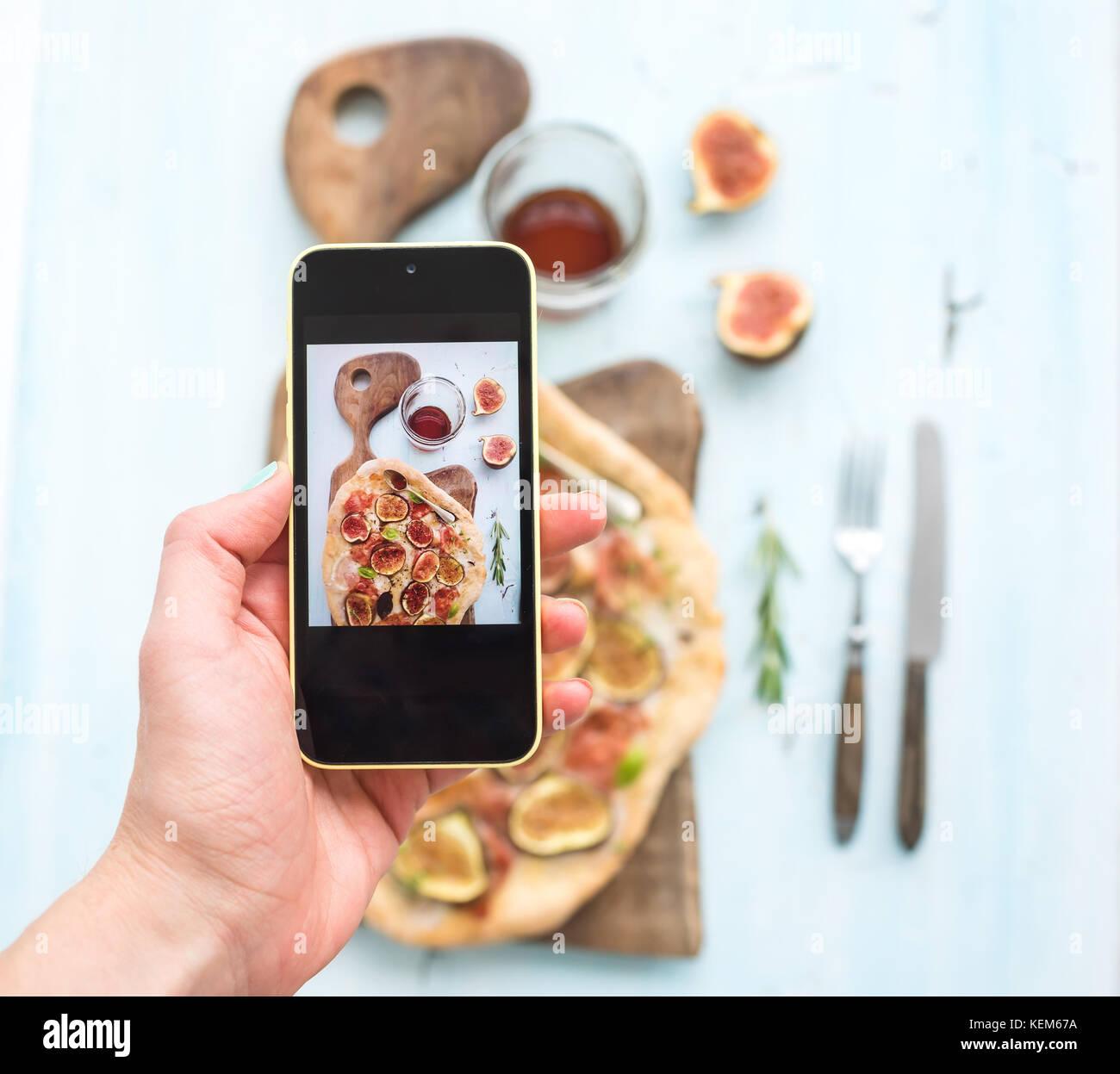 Part faire tourné sur téléphone mobile: pizza maison rustique aux figues, prosciutto et fromage mozzarella, en Banque D'Images