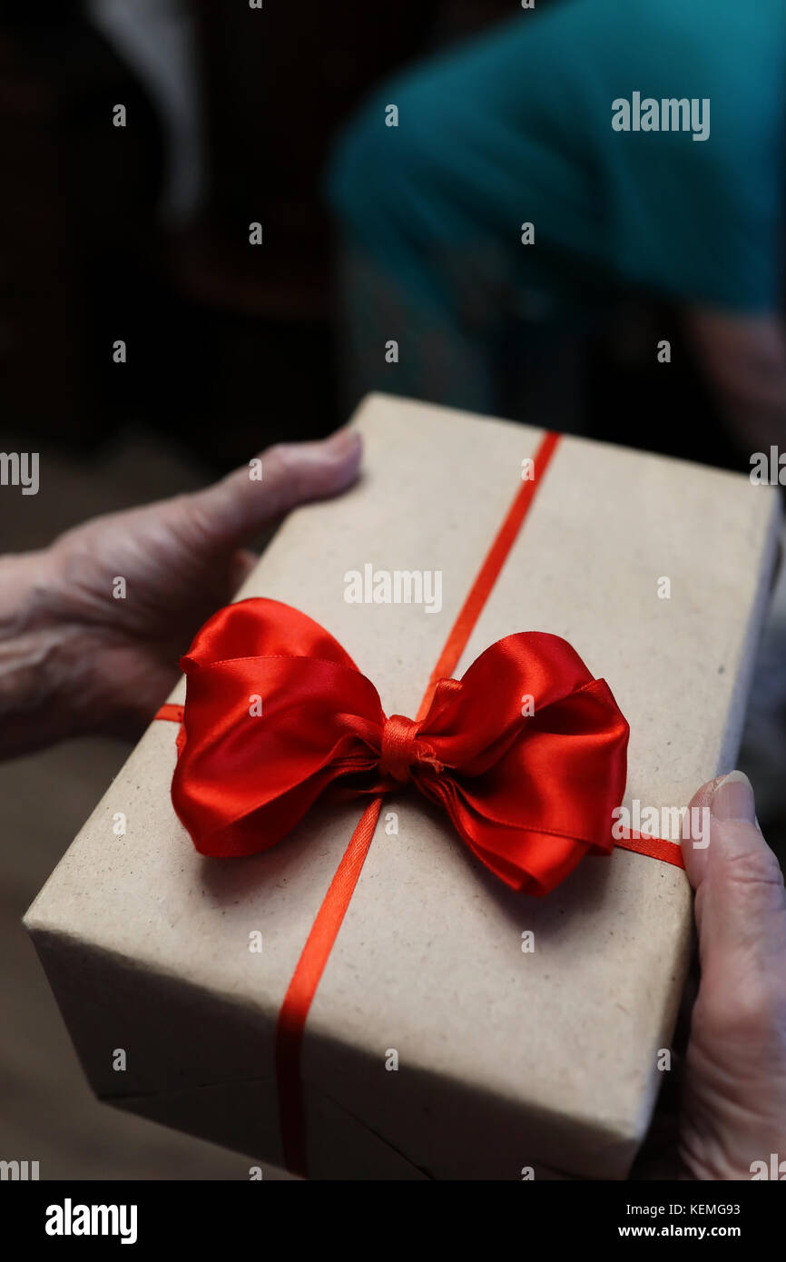 Boîte-cadeau avec arc rouge en grand-mère mains Photo Stock