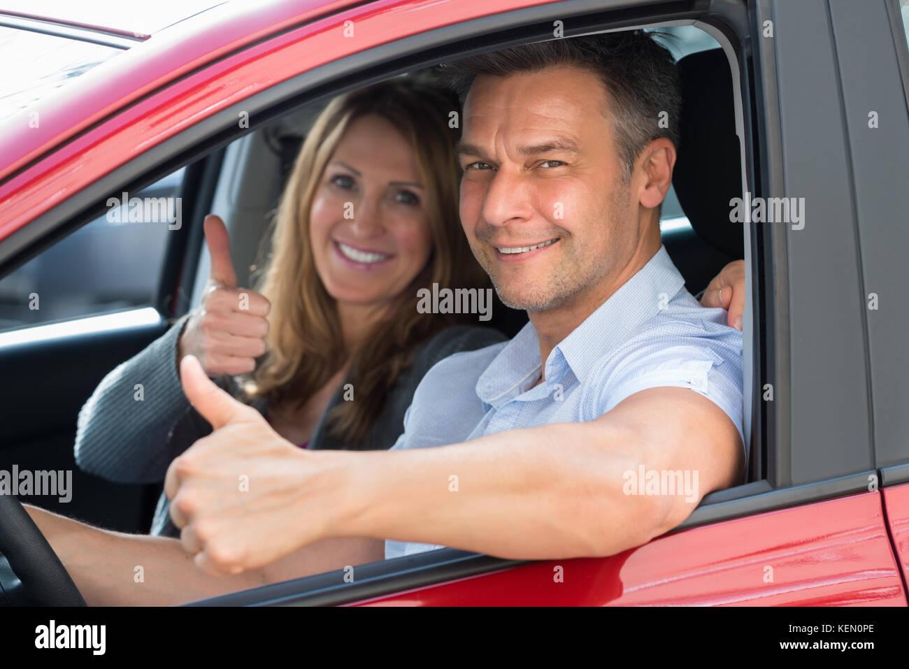 Close-up of happy couple assis à l'intérieur de la voiture nouvellement acheté Photo Stock