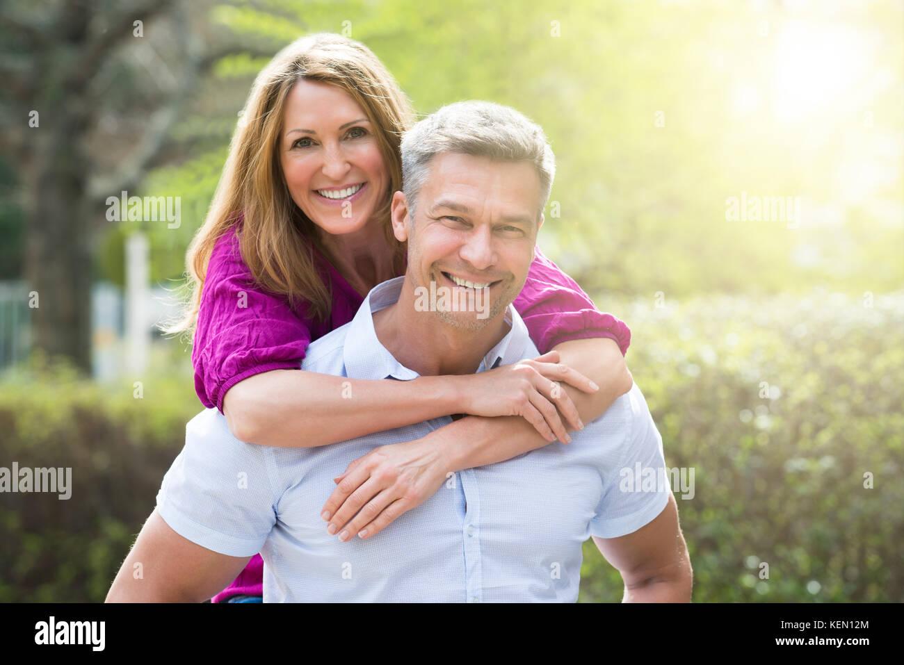 Portrait of happy woman embracing son mari par derrière Photo Stock
