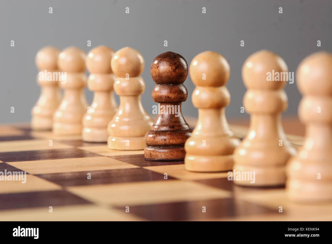 Un pion noir se dresse au milieu d'une rangée de pions blancs, l'autre soulignant ses différentes caractéristiques de l'acceptation du groupe. Banque D'Images