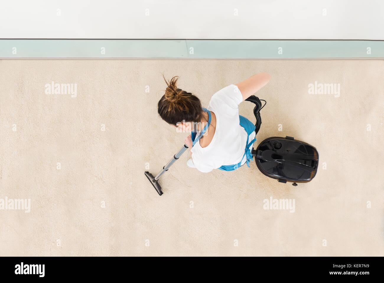 Les jeunes femmes en uniforme de l'aspirateur nettoyeur marbre Photo Stock