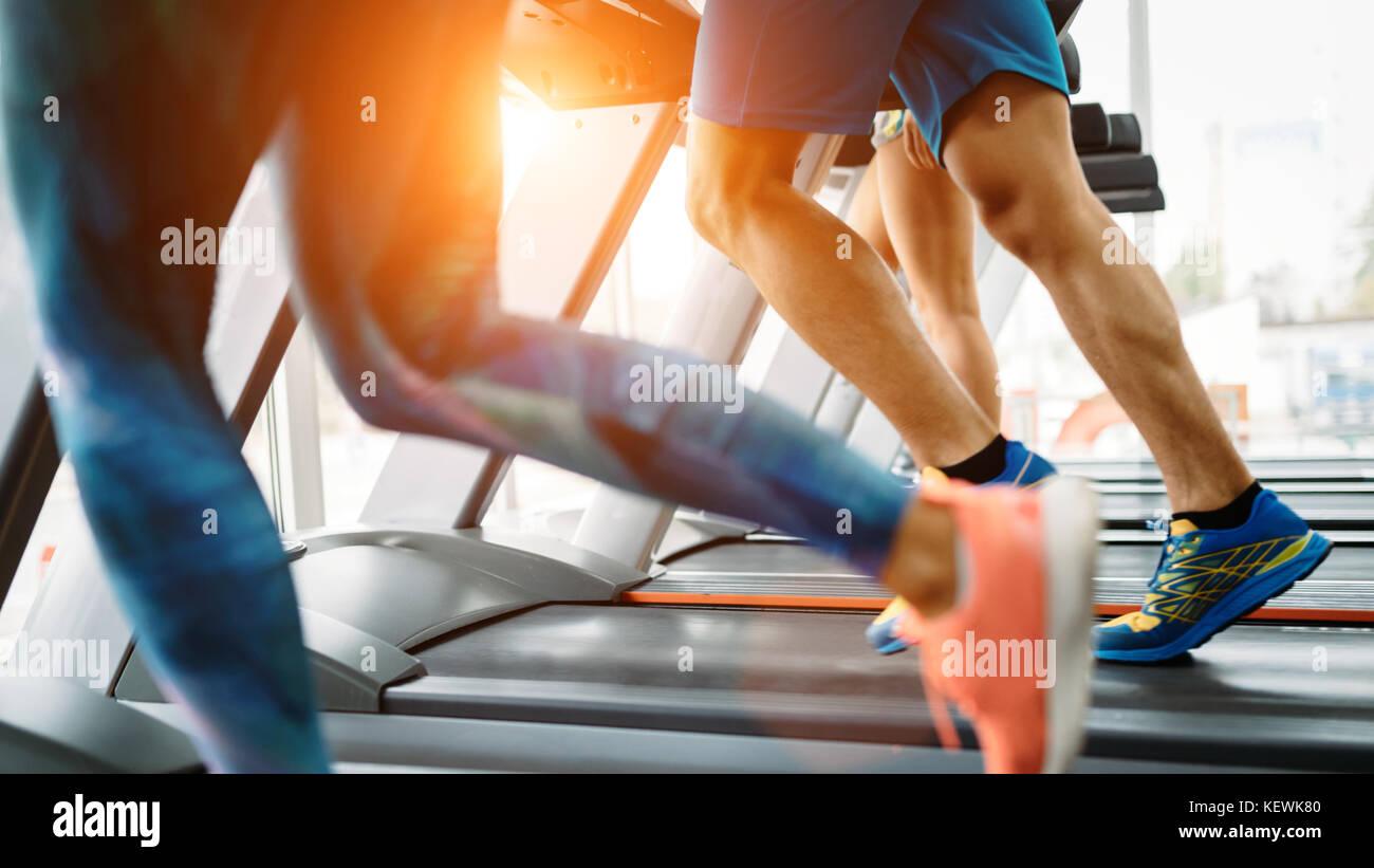 Photo de personnes fonctionnant sur tapis roulant dans une salle de sport Photo Stock