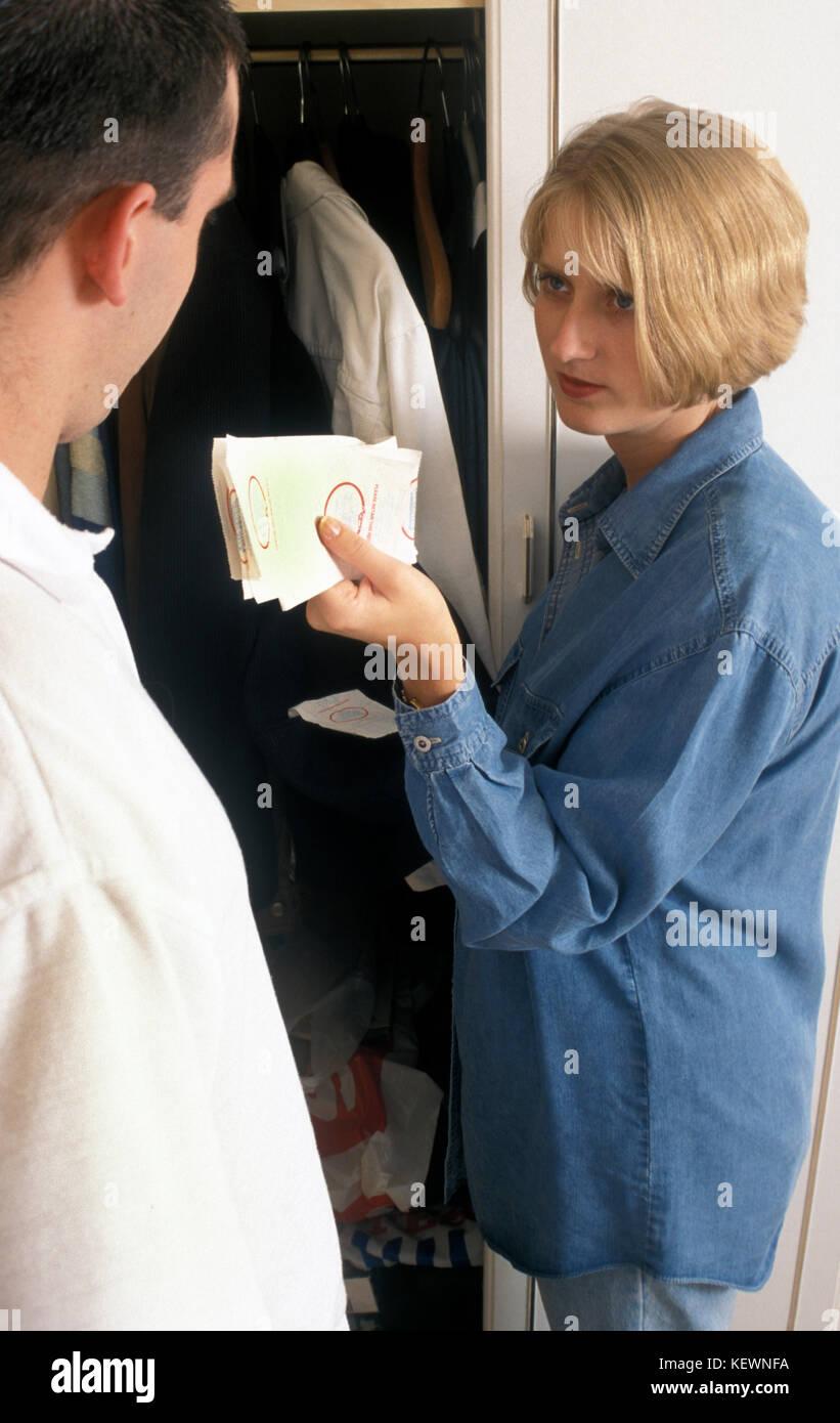 Femme mari confronte comme elle le trouve reçus suspect caché dans ses poches Banque D'Images