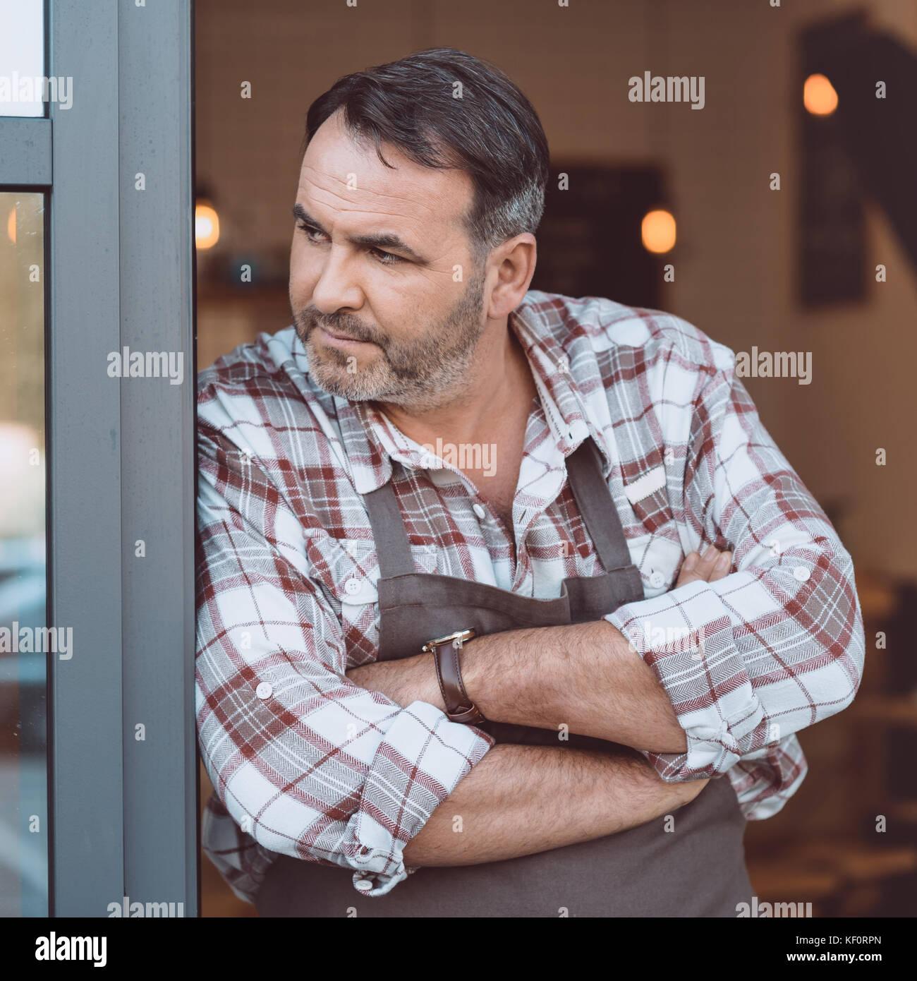 Barman s'appuyant sur entrée de cafe Photo Stock