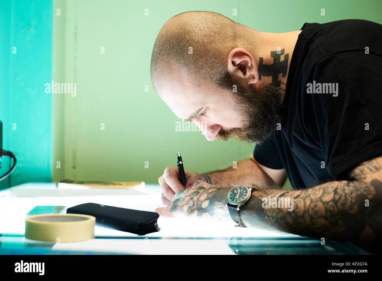 Londres, Royaume-Uni, Tatoueur au travail dans son studio d'affaires locaux, Tatoueur Photo Stock