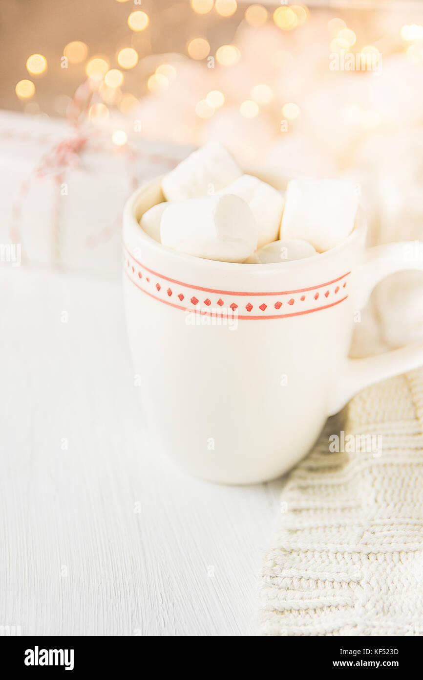 Mug blanc avec du chocolat chaud boisson cacao et les guimauves sur le dessus. sparkling garland lights en arrière Photo Stock