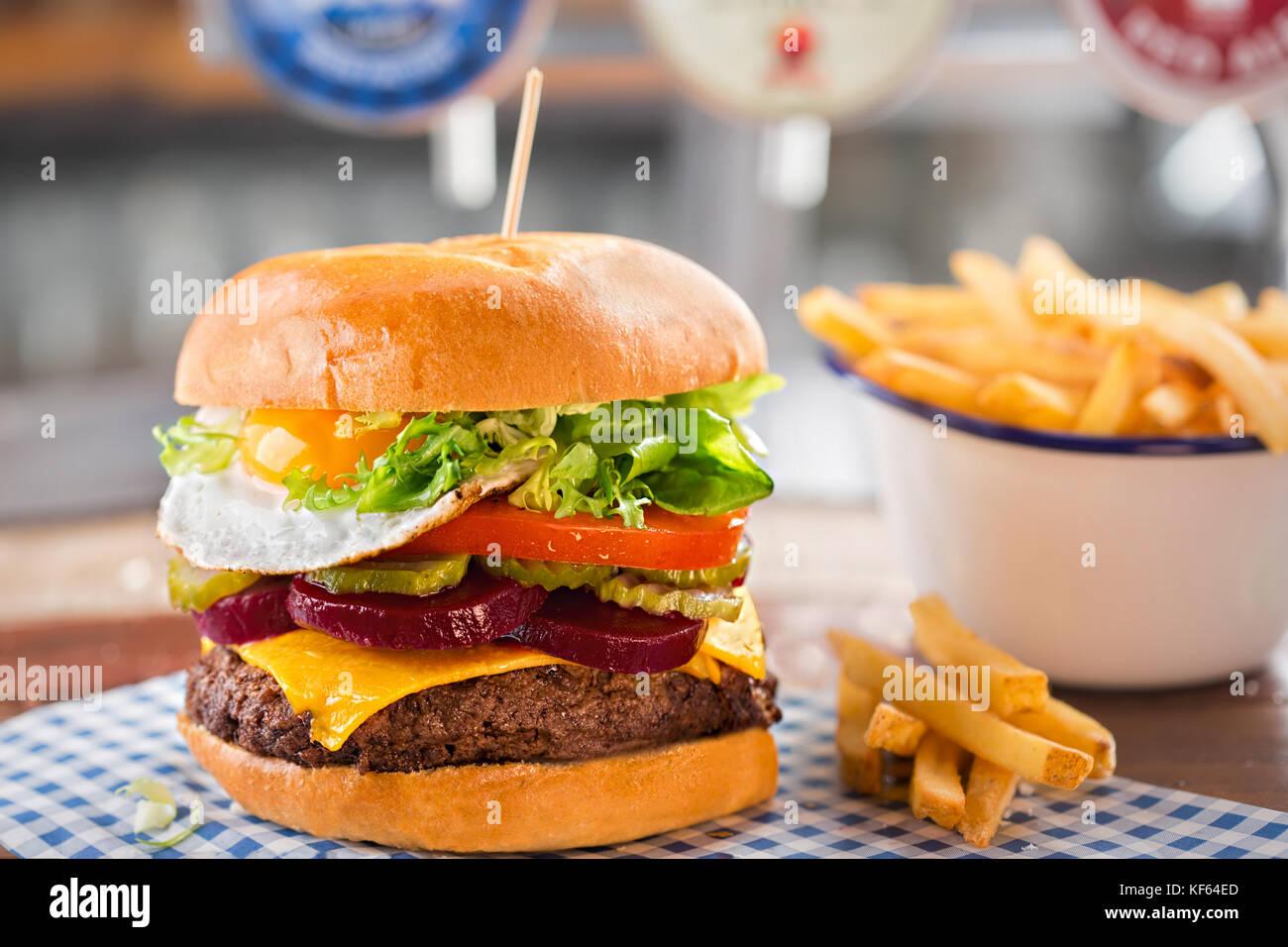 Burger de boeuf au fromage, laitue, tomate, betterave & cornichon, surmonté d'un œuf frit Photo Stock
