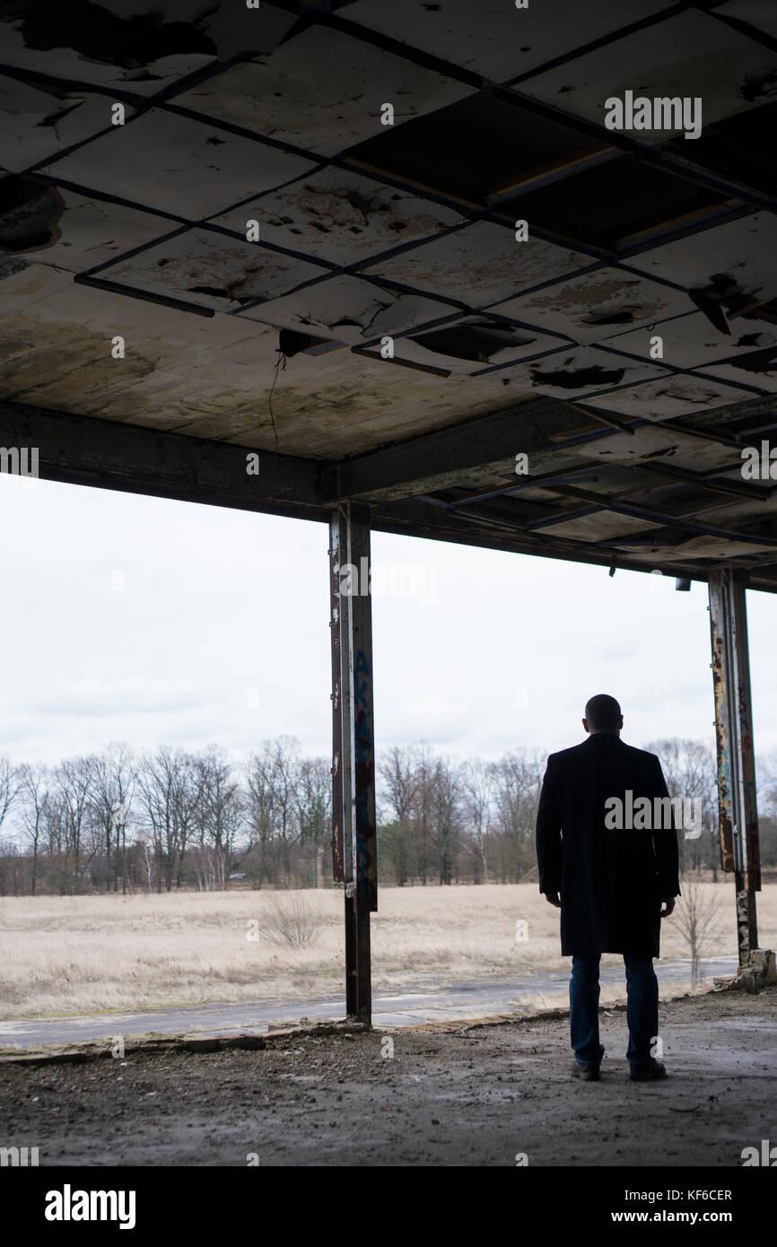 Vue arrière d'un homme portant un manteau debout à l'intérieur d'un bâtiment abandonné Photo Stock
