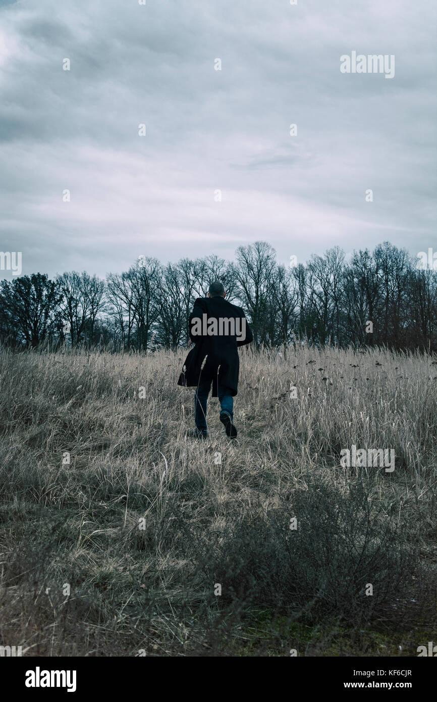 Vue arrière d'un homme en fuite dans un champ Photo Stock