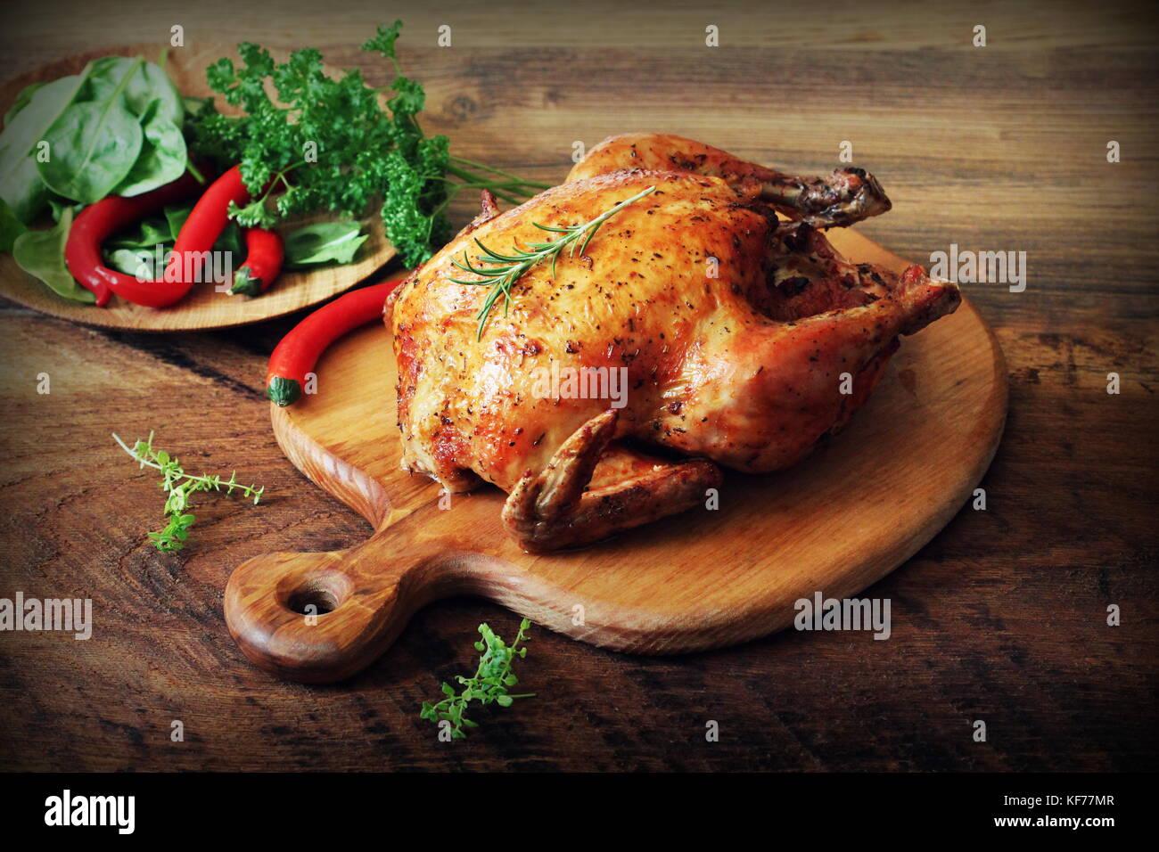Poulet rôti entier sur une planche à découper en bois fond rustique. Photo Stock