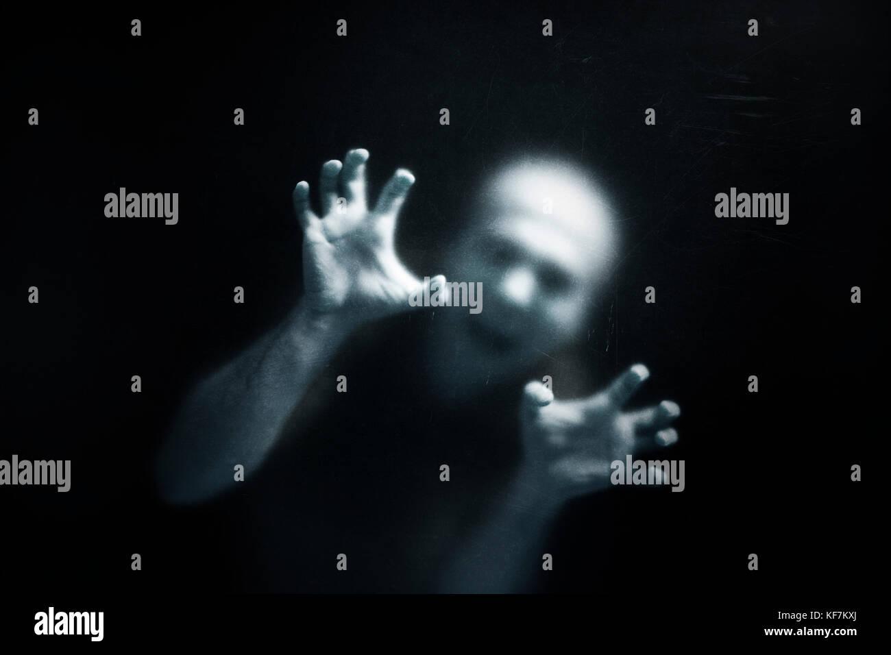Homme qui crie derrière un verre rayé poussiéreux Photo Stock
