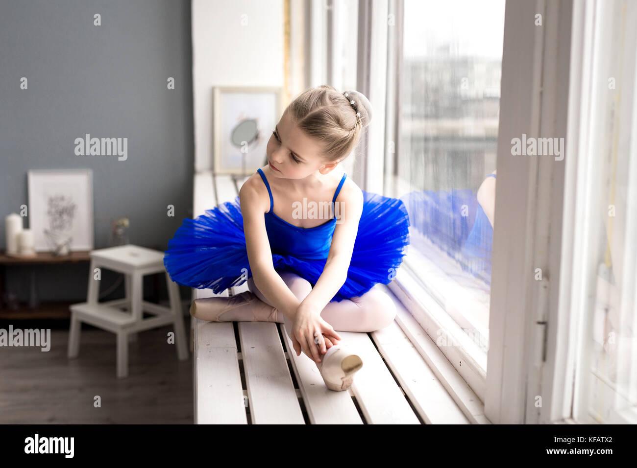 Petite fille rêve de devenir une ballerine. La jeune fille dans un costume de danse ballet bleu dans une chambre. Photo Stock
