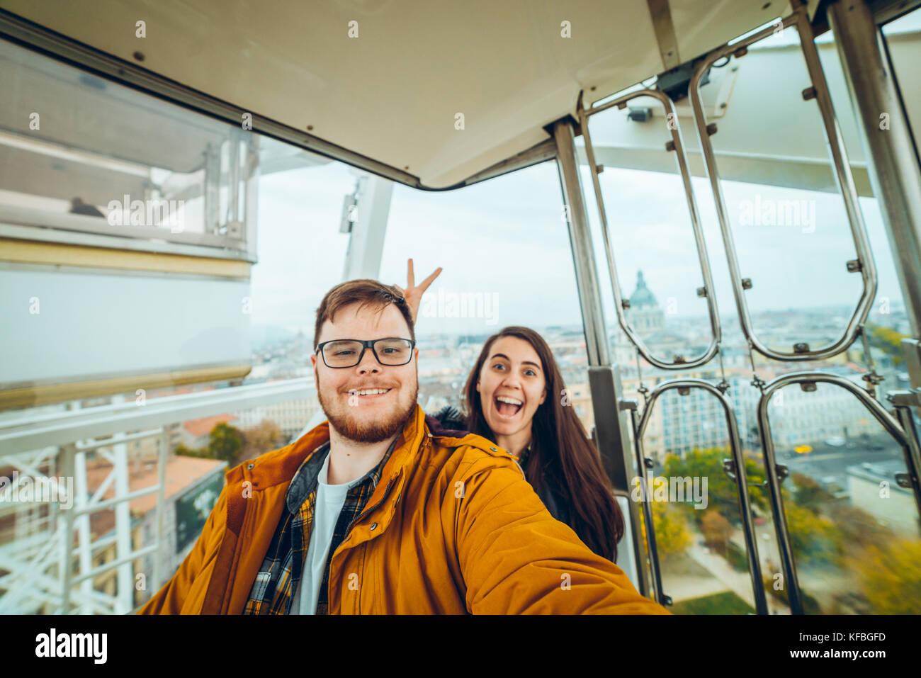 Homme avec femme à prendre une grande roue selfies Photo Stock