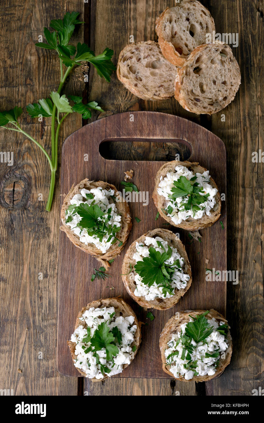 Des sandwichs avec du fromage et des herbes vertes, vue du dessus, country style Photo Stock