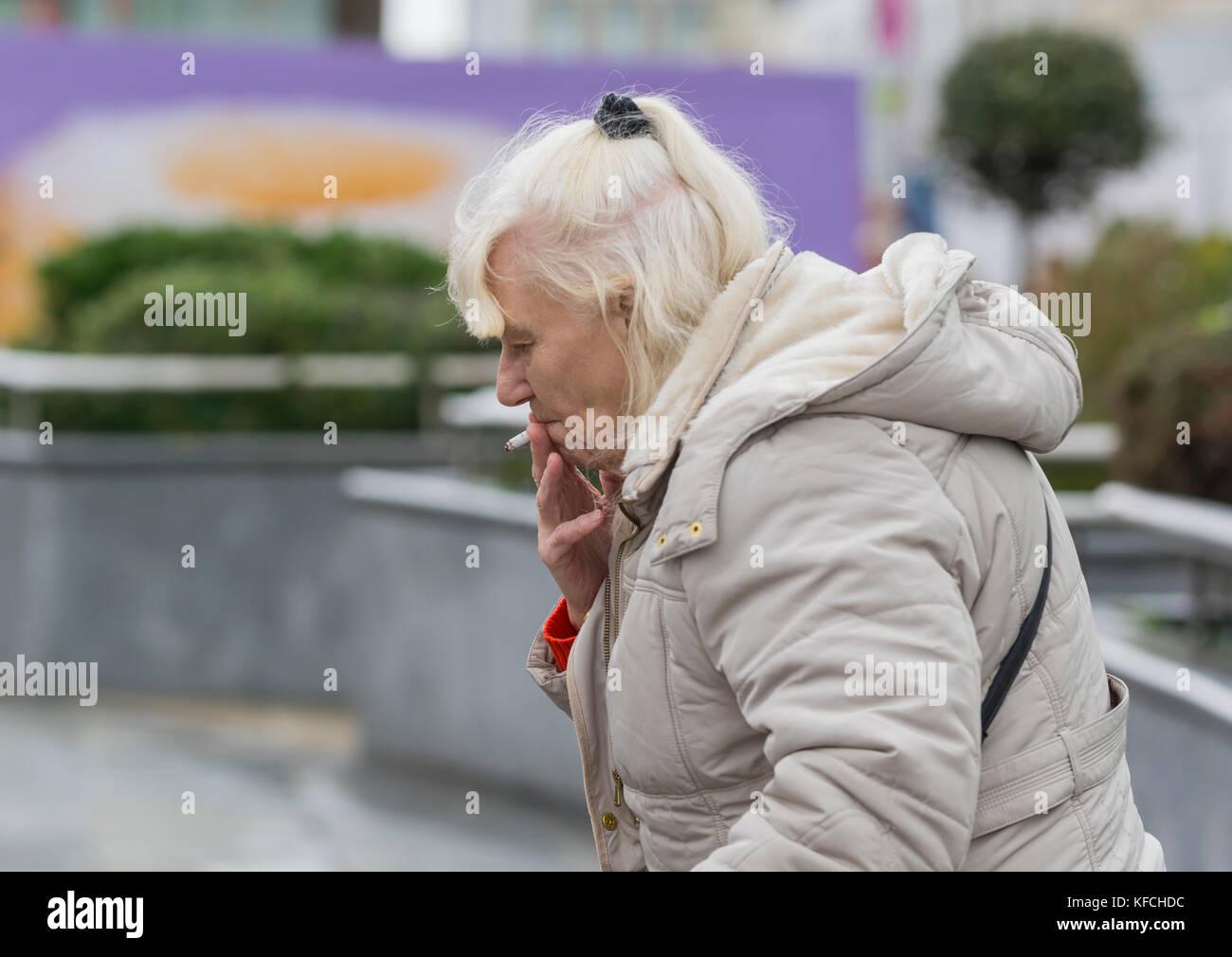 Femme âgée fumer une cigarette à l'extérieur du Royaume-Uni. Photo Stock