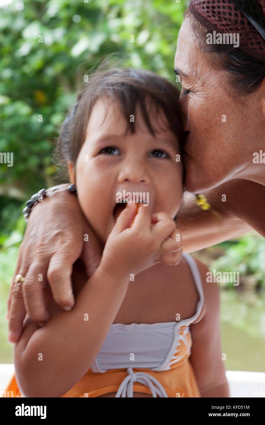 Raiatea, Polynésie française. Grand-Mère embrassant son petit-enfant tout en montant un bateau le Photo Stock