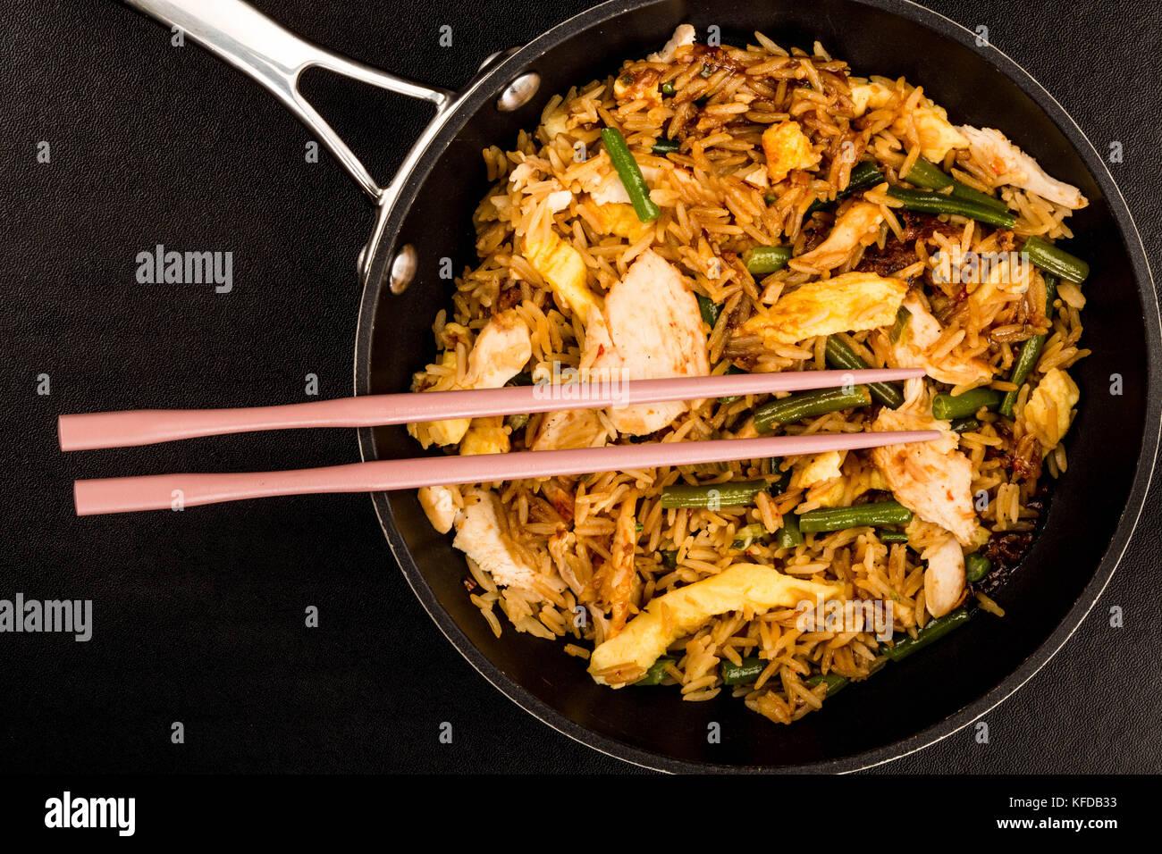 Style indonésien nasi goreng Poulet et riz repas contre un fond noir avec baguettes Photo Stock