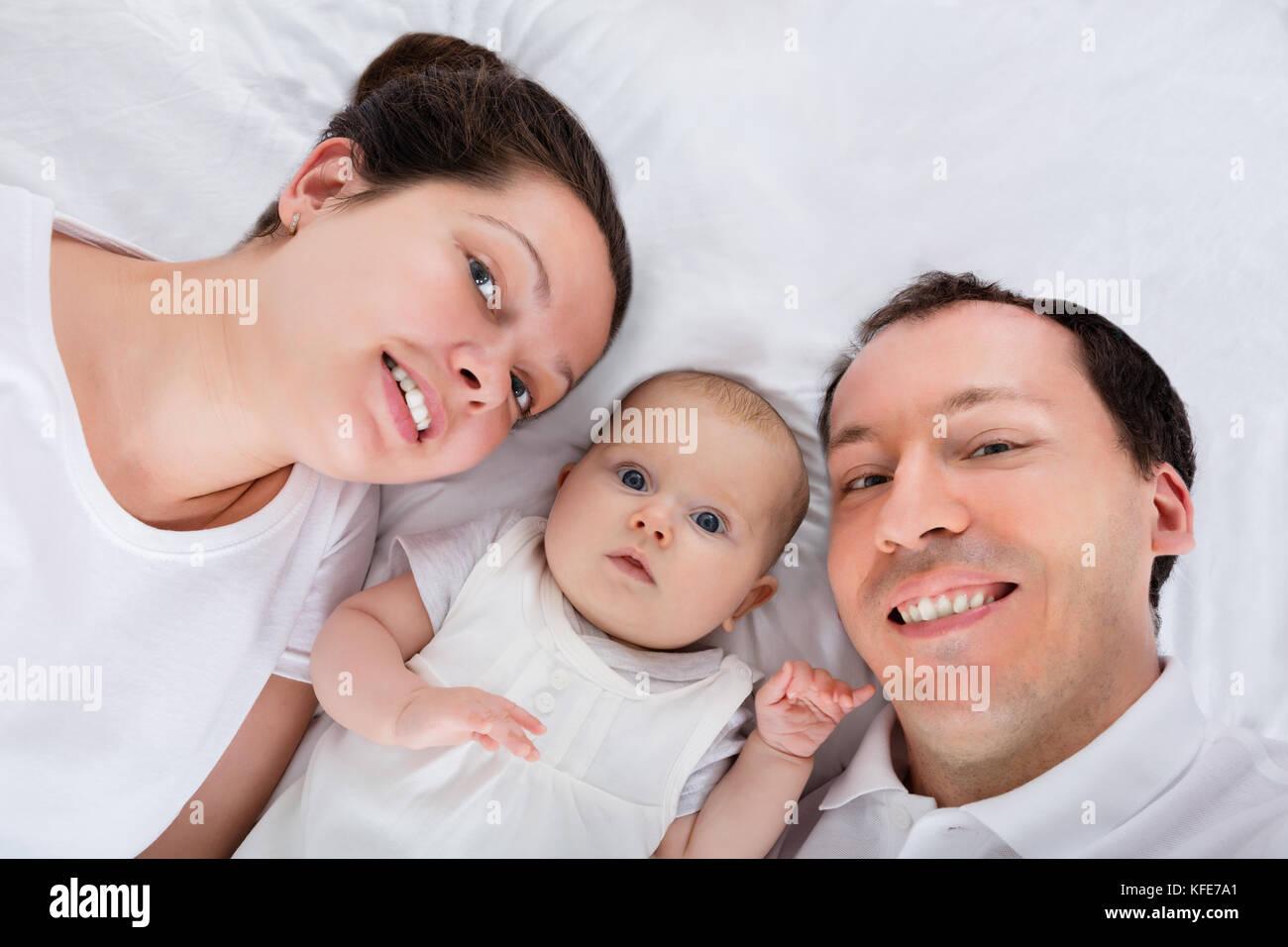 Portrait d'une famille heureuse sur lit blanc Photo Stock