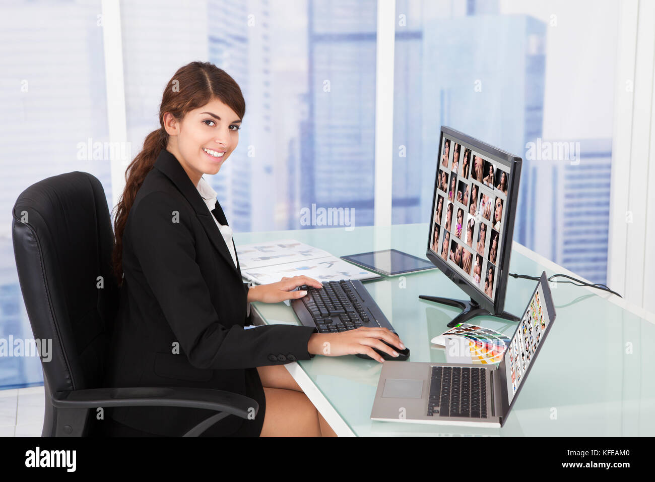 Young businesswoman looking at color swatches at computer desk in office Photo Stock