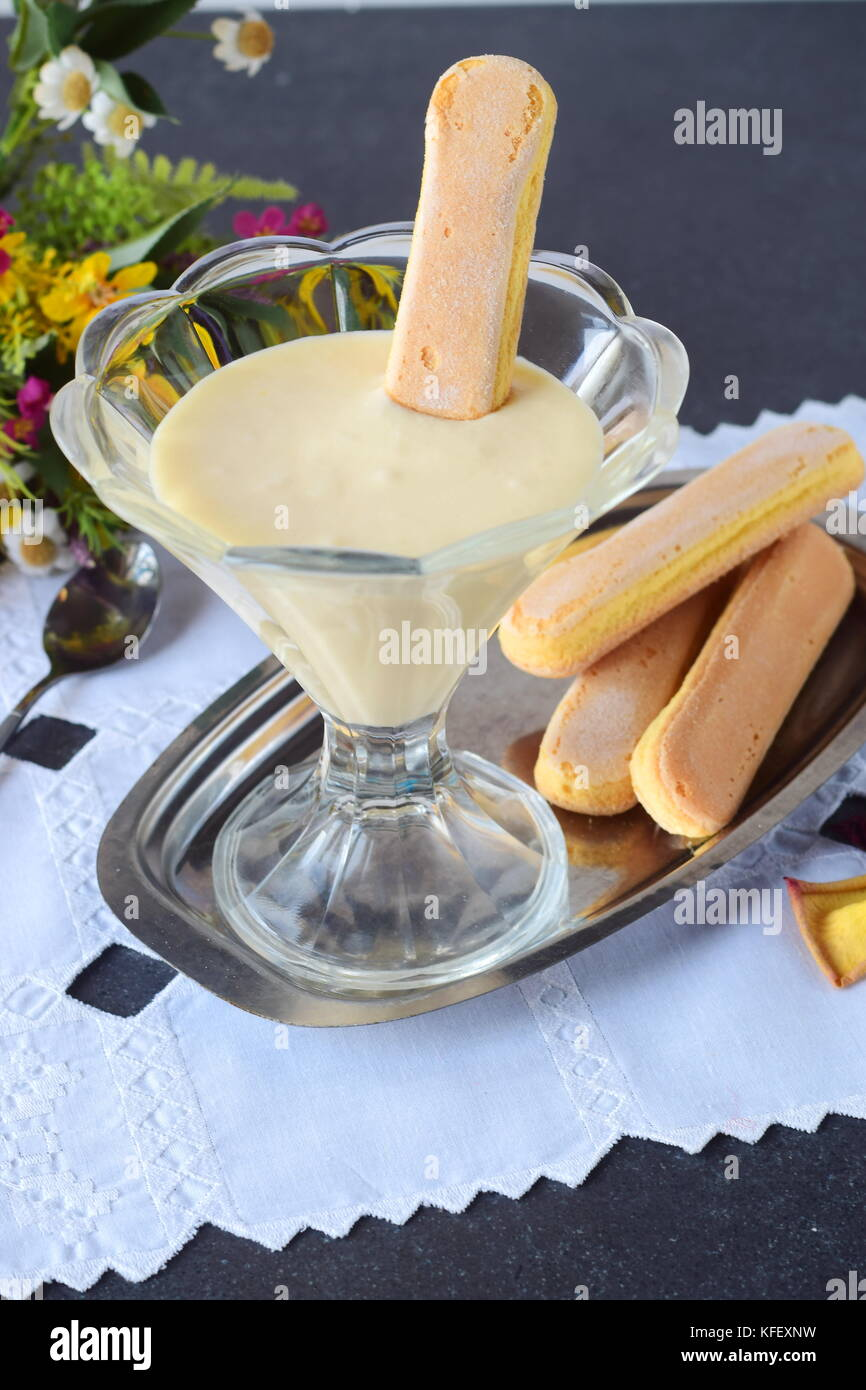 Pour la crème tiramisu dessert italien dans un bol en verre avec des biscuits Photo Stock