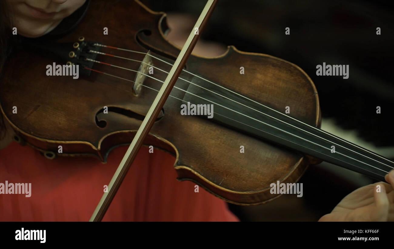 Main de la jeune fille sur les cordes d'un violon. main de la jeune fille sur le manche du violon. Photo Stock