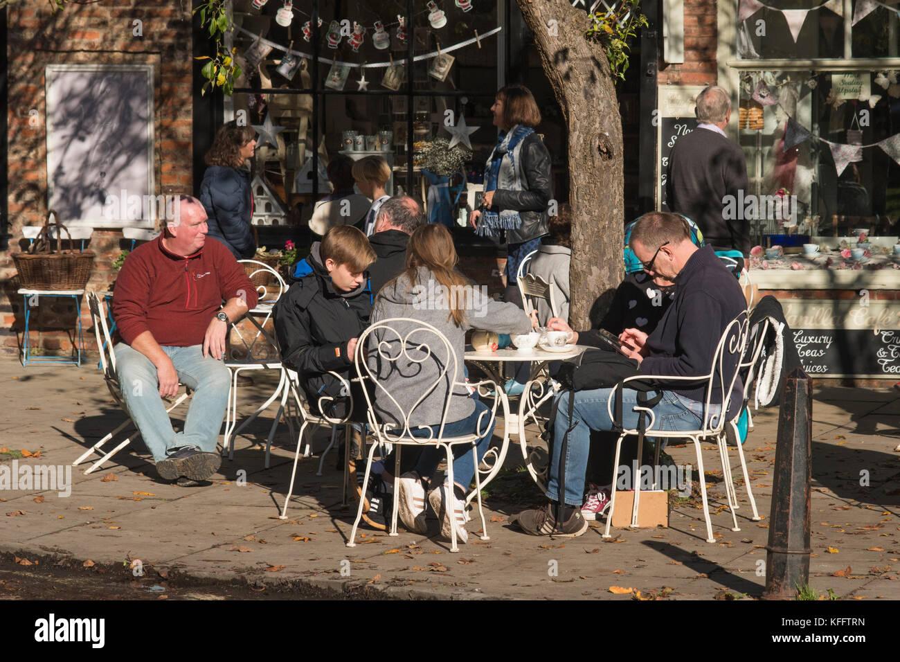 Tables & chaises à l'extérieur d'un café et les gens en vacances profitant de soleil d'automne, s'asseoir, se détendre Banque D'Images