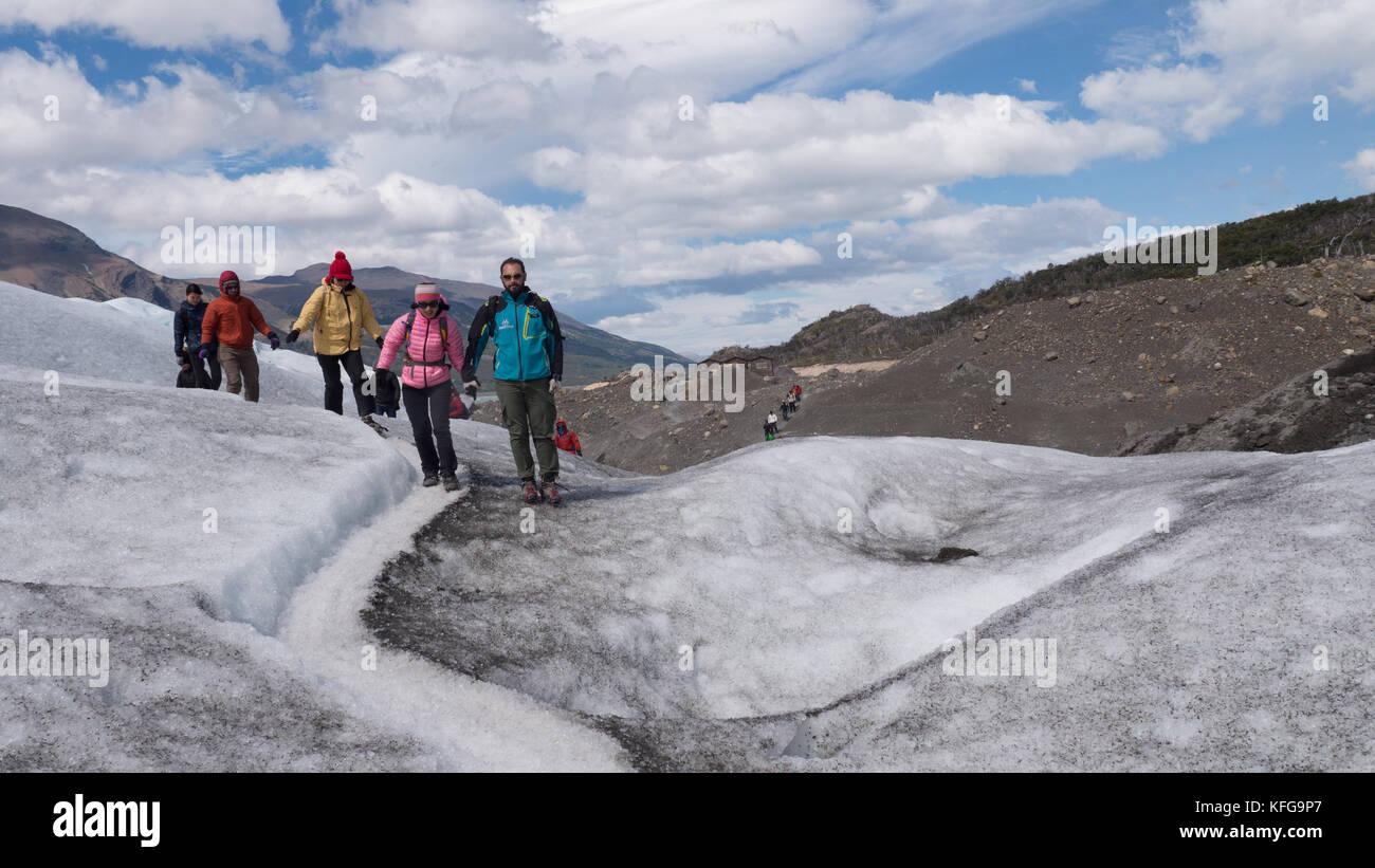 Des guides d'un groupe de touristes habillés de couleurs vives sur une courte randonnée glaciaire avec ciel bleu, paysages glaciaires, exécutant des ruisseaux et des pics glaciaires Banque D'Images