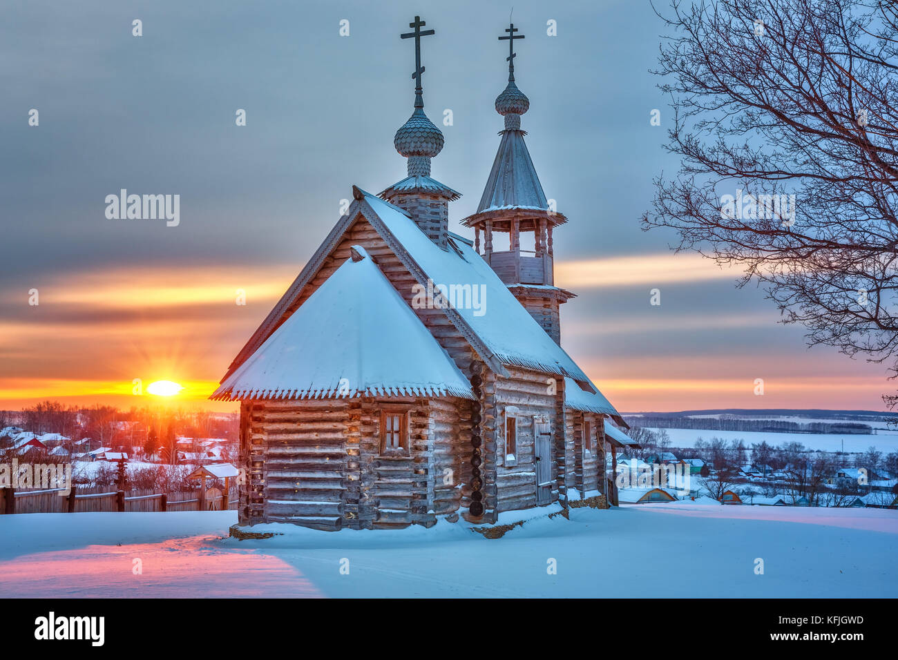 Petite église russe au coucher du soleil en hiver Photo Stock