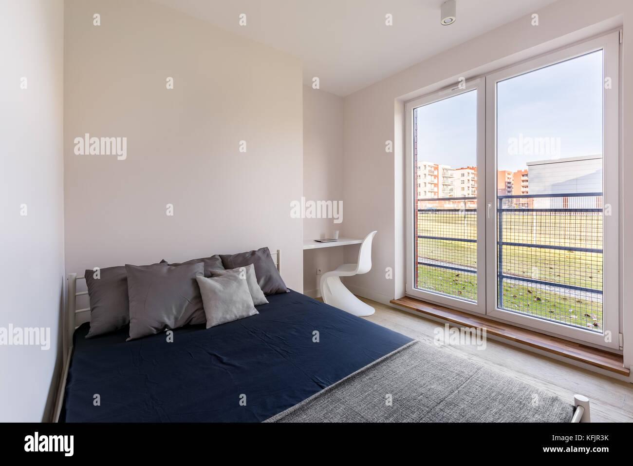 Chambre simple avec un petit bureau une chaise un lit double et