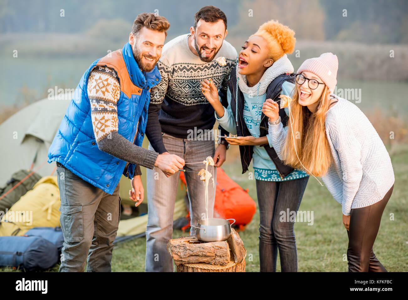 Amis de chandails de manger en plein air à fondue Photo Stock