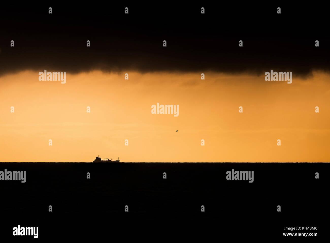 Coucher du soleil - la silhouette d'un navire contre un coucher de soleil. Photo Stock