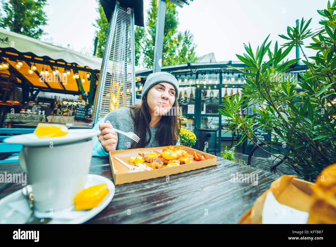 Belle femme manger en café à l'extérieur Photo Stock