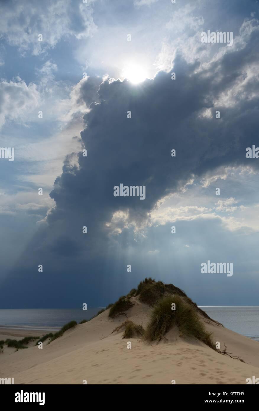 Soleil d'inspiration sortir de nuages sur dune de sable Photo Stock
