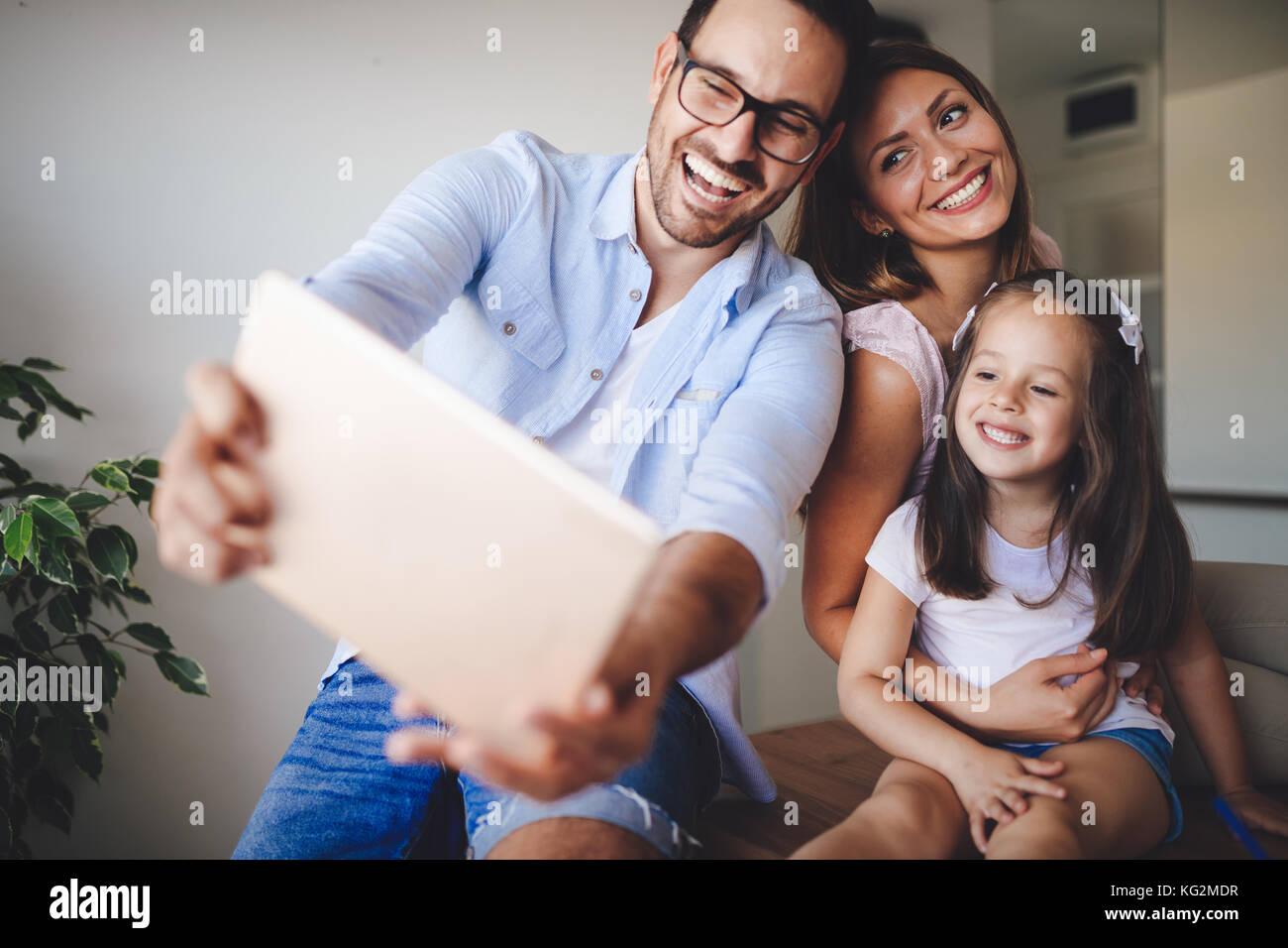 Famille heureuse de prendre dans leur maison selfies Photo Stock