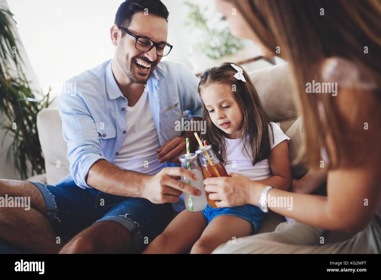 Boire du jus de la famille heureux ensemble dans leur maison Photo Stock