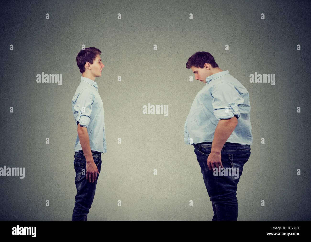 Jeune homme cintrée à la graisse à lui-même. Le choix des aliments nutrition concept de vie Photo Stock