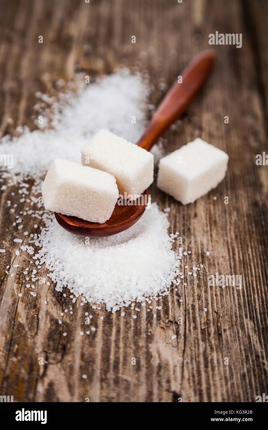 Cuillère en bois avec du sucre sur un vieux fond de bois Photo Stock