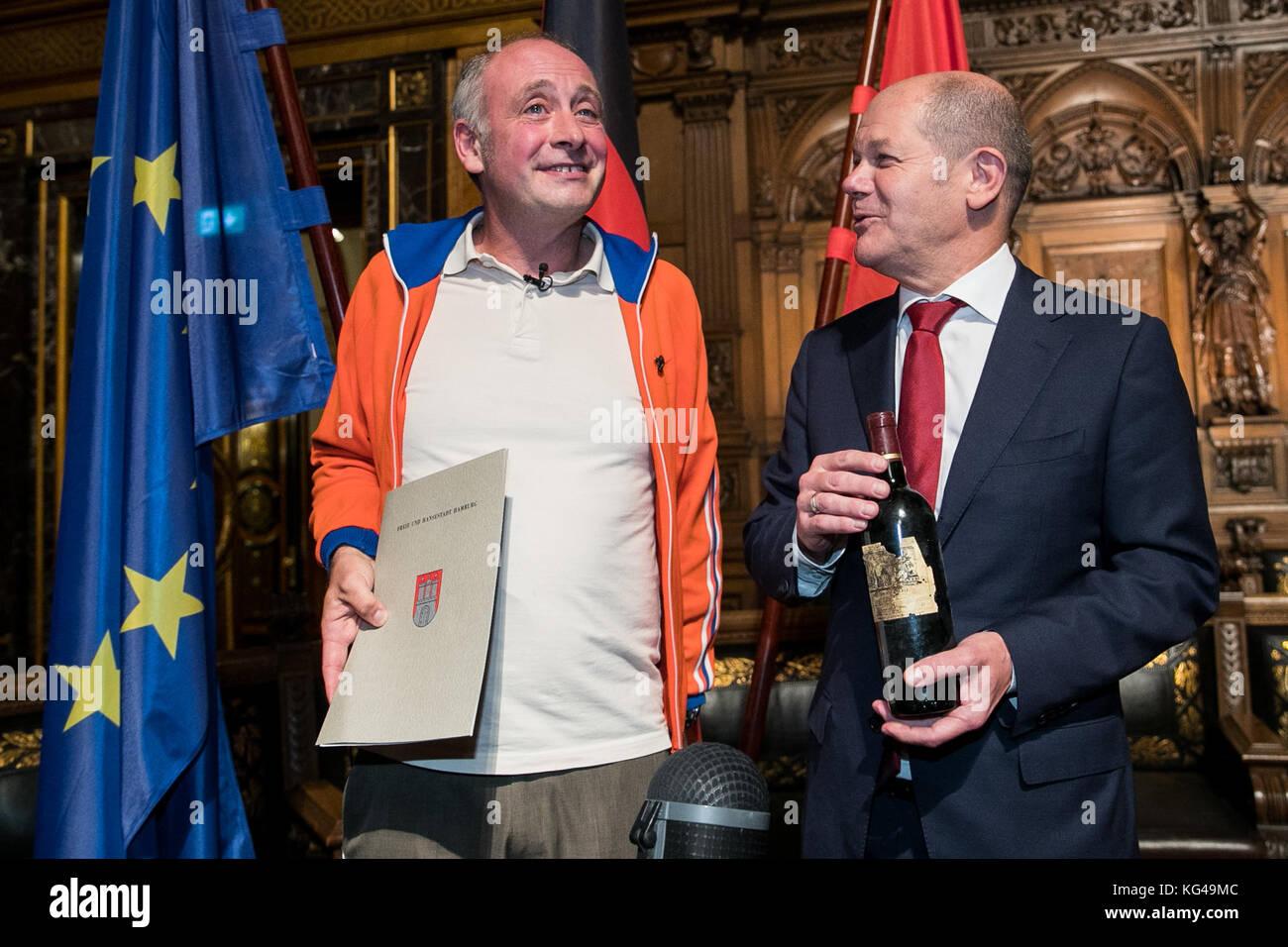 L'artiste de cabaret, Emmanuel peterfalvi (l), présente une bouteille de vin rouge pour le premier maire de Hambourg d'Olaf Scholz le parti social-démocrate d'Allemagne (SPD) après la 42e cérémonie de naturalisation dans le grand hall de l'hôtel de ville de Hambourg le 03 novembre 2017. Le comédien de paris connu sous le nom de alfons a obtenu la citoyenneté allemande vendredi. plus de 100 autochtones de Hambourg ont célébré leur naturalisation à l'hôtel de ville cérémonie. photo: christian charisius/dpa Banque D'Images