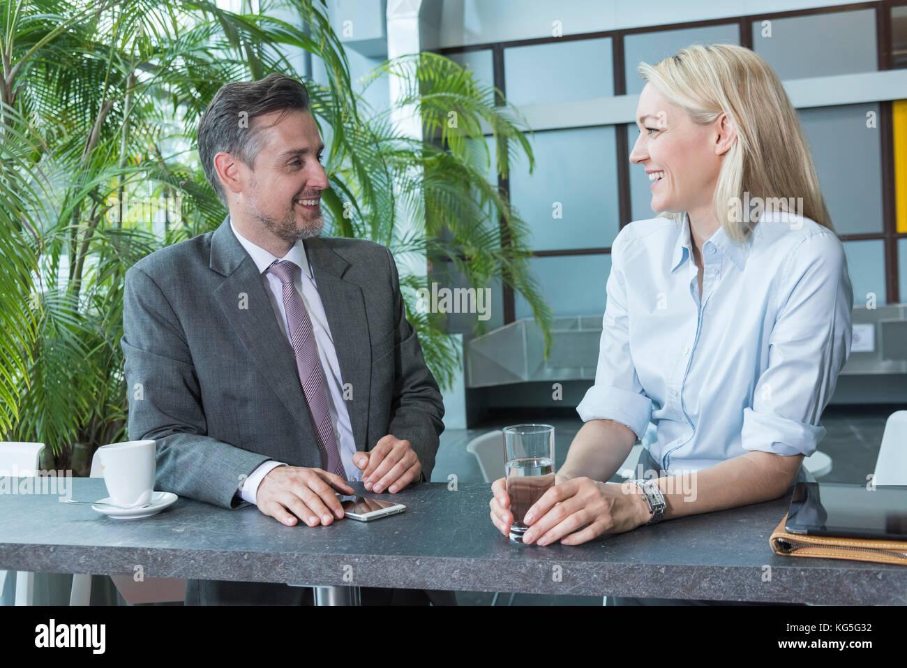 Les gens d'affaires, l'homme et la femme dans la conversation, rire, flirt Photo Stock