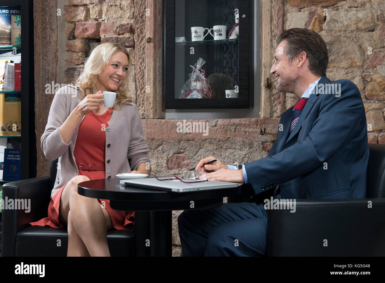 L'homme et la femme à la table dans le hall de l'hôtel, boire un expresso, Sourire, contact avec Photo Stock