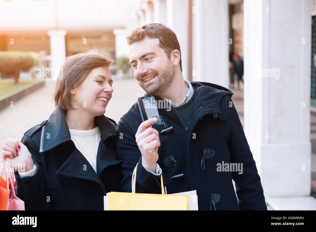 Homme tenant une carte de crédit prêt pour le shopping de temps avec sa petite amie Photo Stock