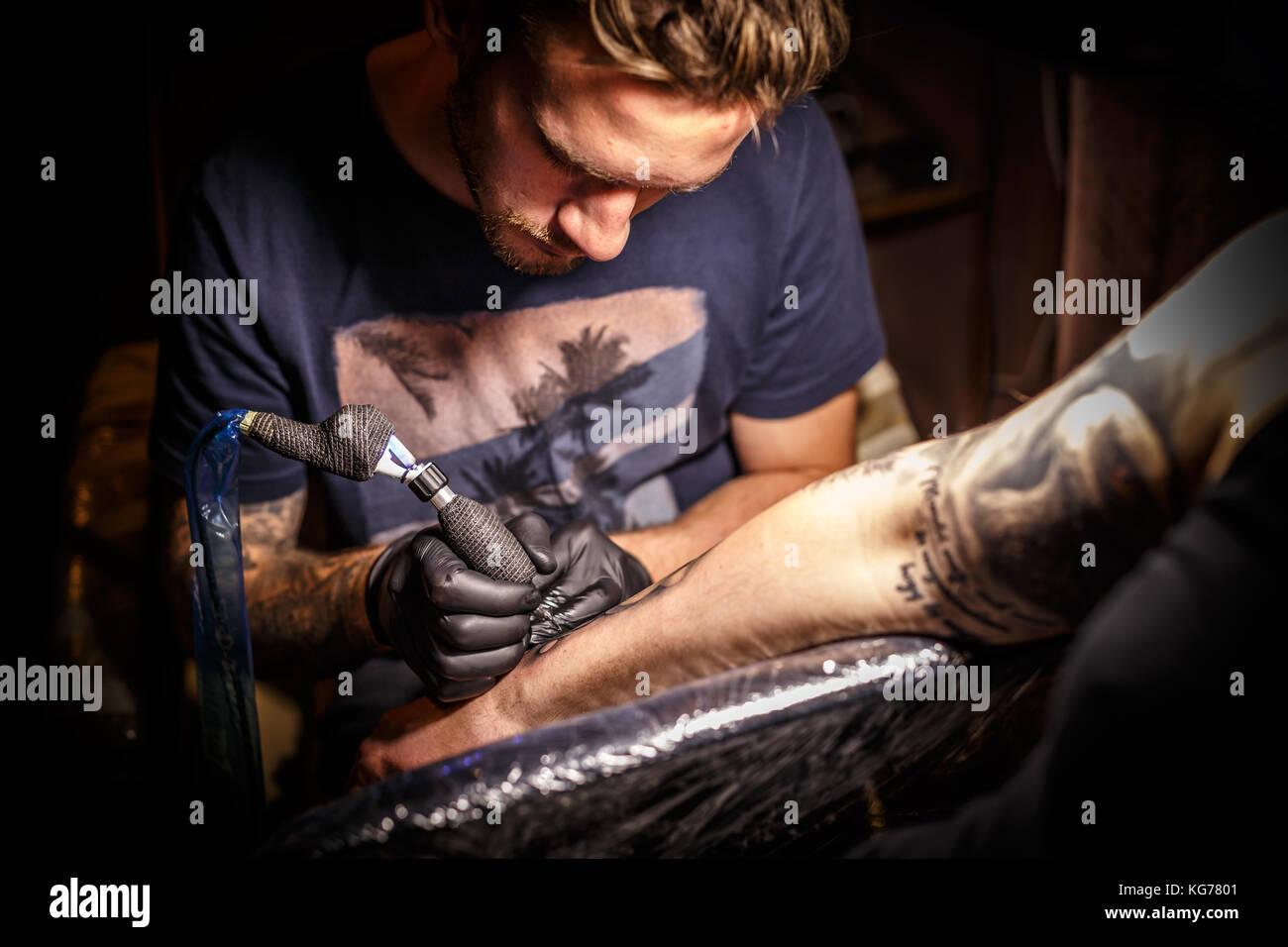 Tatoueur professionnel à travailler dans un studio de tatouage. Photo Stock