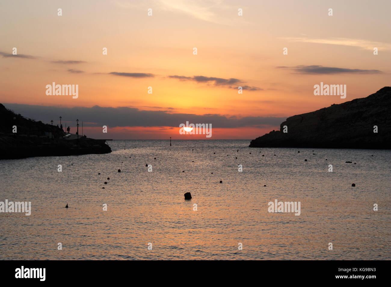 Coucher de soleil sur la mer Méditerranée, comme vu de la station balnéaire de Xlendi à Gozo, Photo Stock