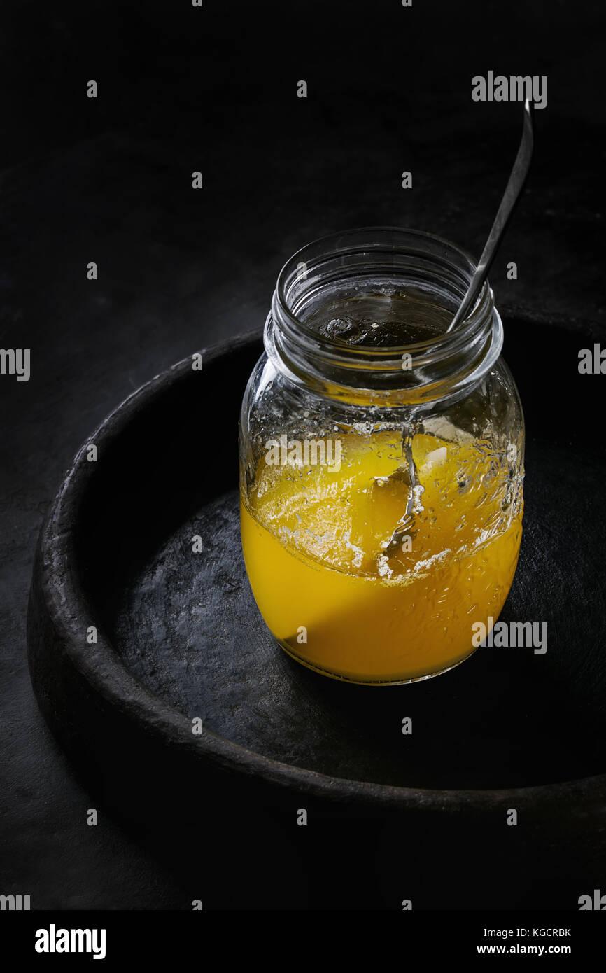 Verre de beurre ghee Photo Stock