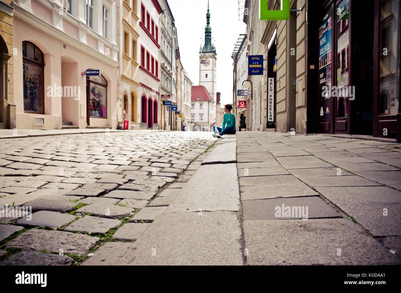 Femme assise seule sur le trottoir dans une rue d'Olomouc, avec l'hôtel de ville en arrière-plan Photo Stock