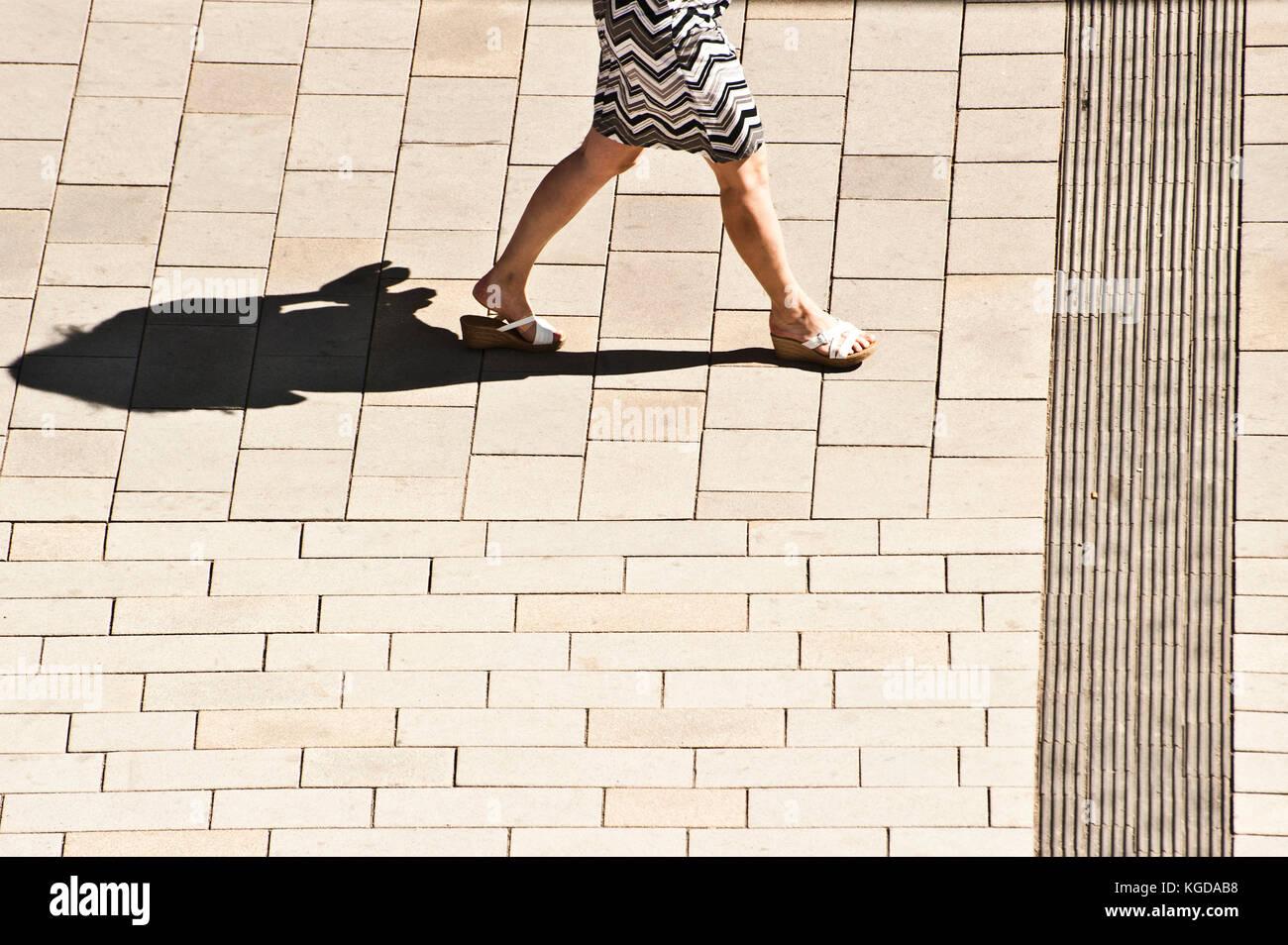 Les jambes d'une femme en jupe à la rue et l'ombre Photo Stock