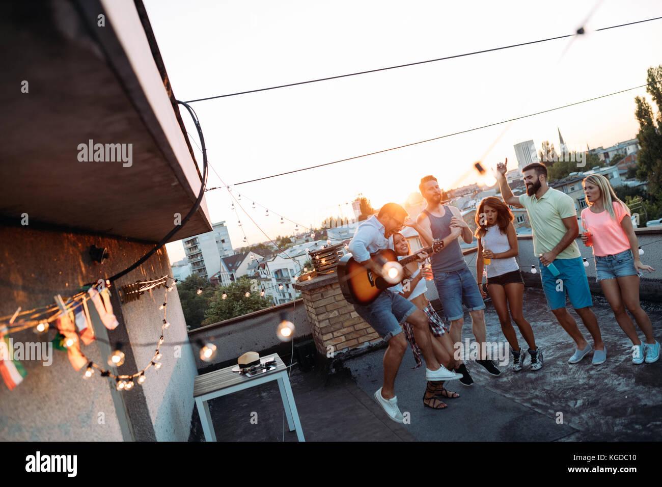 Groupe d'happy friends having party sur le toit Photo Stock
