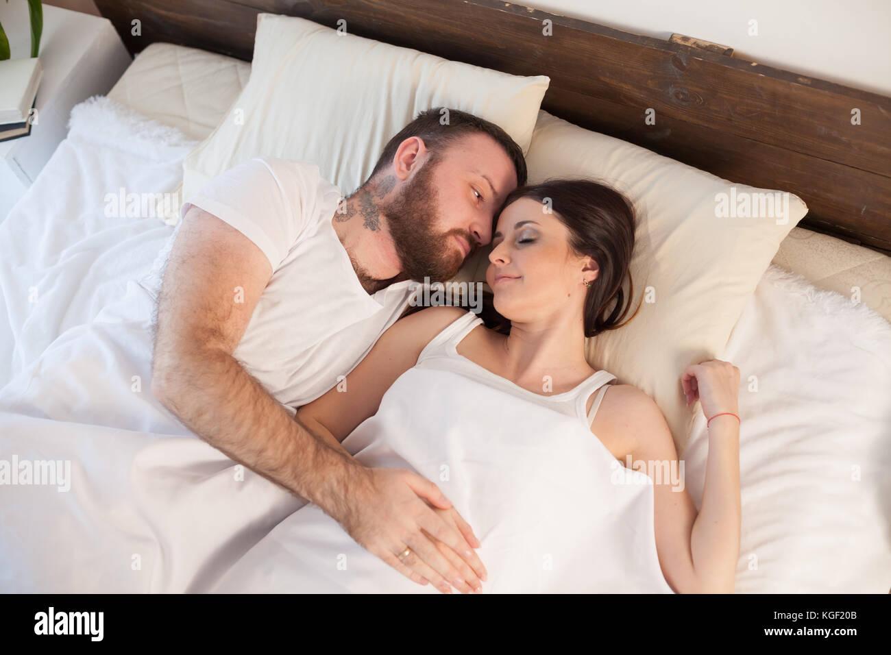L'homme se réveille une femme dans la chambre le matin week-end Photo Stock